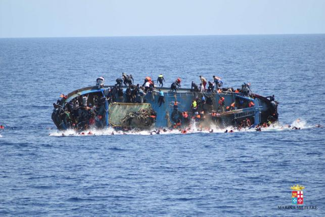 "Migrants are seen on a capsizing boat before a rescue operation by Italian navy ships ""Bettica"" and ""Bergamini"" off the coast of Libya in this handout picture released by the Italian Marina Militare on May 25, 2016. Marina Militare/Handout via REUTERS"