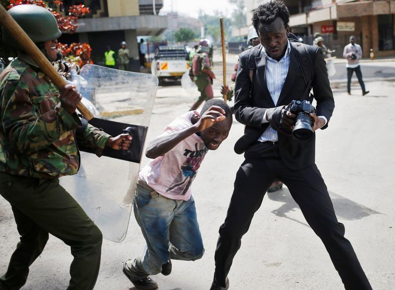 Cameraman is caught up in a fracas. Police officer is seen beating up a protestor in Kenya. (Photo, HRW)